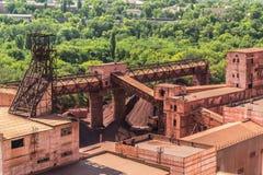 Industriella konstruktioner bredvid den gröna växten fotografering för bildbyråer