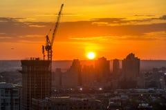 Industriella konstruktionskranar och byggnadssilhouettes över sunen på soluppgången royaltyfri foto