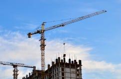 Industriella konstruktionskranar och konturer av arbetare under installation av formwork royaltyfri bild