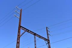 Industriella kraftledningar mot blå himmel Arkivfoton