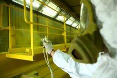Industriella måla delar Målaren målar järnbeståndsdelen i guling royaltyfri fotografi