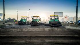 Industriella maskiner som lägger asfalt på den nya vägen Royaltyfri Foto