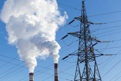 Industriella rör med rök och den elektriska linjen Royaltyfri Bild