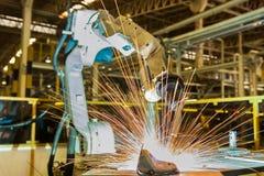 Industriella robotar svetsar den automatiska delen för enheten i bilfabrik Royaltyfri Foto