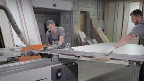 Industriella snickarearbetare som arbetar på den bitande wood maskinen stock video