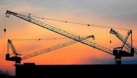 Industrielle Aufbaukräne und Gebäudeschattenbilder über Sonne am Sonnenaufgang stockbilder