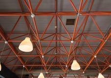 Industrielle Decke mit roten Trägern und Lampen stockfotos