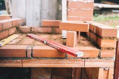 Industrielle Details der Maurerarbeit, des Niveaus und der Ziegelsteine auf Baustelle Stockfotos
