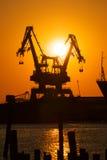 Industrielle Kräne am Sonnenuntergang Lizenzfreie Stockfotos