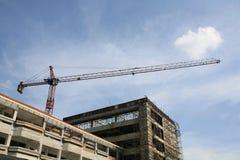 Industrieller Aufbau: roter Kran mit blauem Himmel Stockfotografie