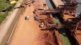 Industrieller Frachthafen mit Radlader-Ladenerz auf Kipplastern, Vogelperspektive stock video