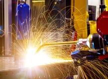 Industrieller gelber Roboterschweißerabschluß - herauf Führungsschweißen von Metallteilen, werden Metalltröpfchen schön herein be lizenzfreie stockfotografie