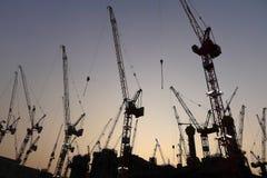 Industrieller Kran an der Baustelle während des Sonnenuntergangs. Lizenzfreie Stockfotos