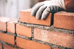 Industrieller Maurer, der Ziegelsteine auf Baustelle installiert
