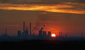 Industrieller Sonnenuntergang mit Fabrikschattenbild Stockfotos