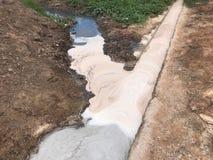 Industrielles Abwasser mit weißem Schaum ist Entladung zum Land, Stockfotos