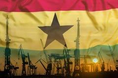 Industriellt begrepp med den Ghana flaggan på solnedgången royaltyfri foto