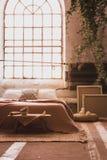 Industriellt fönster i en hemtrevlig sovruminre med en säng, en tabell, ramar och ett element Verkligt foto arkivfoto