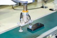 Industriellt gripa robotarbete för närbild för lås ett svart färgsmartphonefall via en transportband arkivfoto