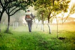 Industriellt jordbruks- - bonde som besprutar giftliga vikter i fruktfruktträdgården för behandling royaltyfri fotografi