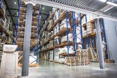 Industriellt lager- och logistikbegrepp Stor lagring med kuggar, hyllor, askar, behållare och annat gods royaltyfria foton