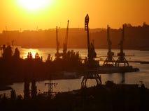 Industriellt landskap för flodport med kranar på en flod Arkivfoto
