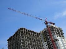 Industriellt landskap: kranar bygger huset mot den blåa himlen royaltyfri fotografi