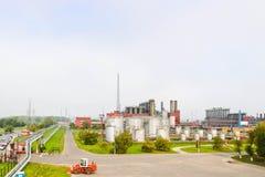 Industriellt landskap med kemiska växter, rör och kolonner Under är en orange traktor Rök kommer från reaktorn arkivfoto
