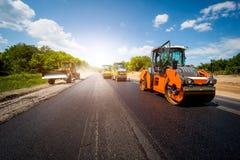 Industriellt landskap med rullar som rullar en ny asfalt i th arkivfoto