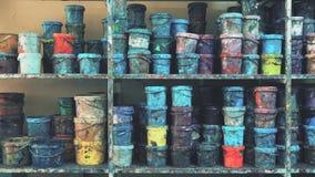 Industriellt målarfärglager mycket av färgrika nedfläckade hinkar stock video