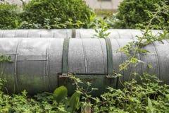 Industriellt metallgasrör i ett grönt gräs arkivfoton