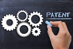 Industriellt patenterat skyddsbegrepp med kugghjul på svart tavla royaltyfri bild