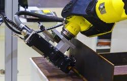 Industrieroboter führt eine Operation des Ausschnittmetalls durch stockbild