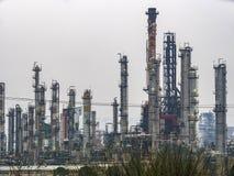 Industriområderaffinaderier under grå färger för molniga himlar Royaltyfria Bilder
