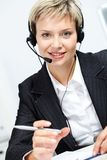 Industrious secretary. Portrait of young attractive secretary with headset looking at camera and smiling Royalty Free Stock Photo