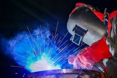 Industry Worker welding steel pipe with sparks light in factory on black background. Industry Worker welding steel pipe with sparks light in factory on black. Industrial Worker at the factory welding process close up by arc weld holder with protective equipment mask, PPE marks welder on dark tone, workman, trained, laboring, connect, tube, pipe, assembly, erection, improvisation, hot, helmet, wear, metal, workshop, structure, manufacture, smoke, job, workplace, flash, fabricate, light, skilled, spark, safety, protection, industry, technical, craftsman, manufacturing, laborer, construction, fire, steel, repair, heavy, metalwork royalty free stock photo