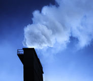 Industry chimney with smoke. Dramatic industry chimney silhouette exausting co2 in the atmosphere Stock Photography