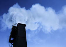 Industry chimney with smoke. Dramatic industry chimney silhouette exausting co2 in the atmosphere Royalty Free Stock Photography