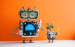 Industry 4.0 concept. Big IT specialist robot with hand wrench and small robotic cyborg. Welcome to the new economic. Future message on blue display. Orange stock photography