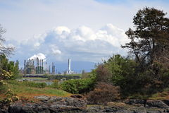 Industry and environment. Beautiful landscape framing a factory in the distance Royalty Free Stock Images