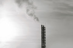 Industry and environmental problems concept - smoke from pipes plant silhouette on sunset Stock Image