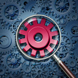 Industry Expertise. And focus as a business concept with gears and cogs connected together as a financial partnership with a red cog in a magnifying glass as an royalty free illustration