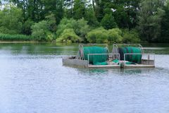 Industry fishing rig with rolled net. On a lake with forest in background. Malente, Germany royalty free stock photo