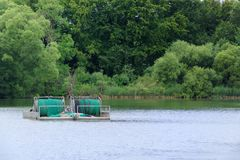 Industry fishing rig with rolled net. On a lake with forest in background. Malente, Germany stock photo