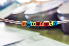 Industry of multicolored letters on the background of the drawings and turning and grinding parts at a machine-building enterprise.  stock image