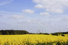 Industry and nature. Yellow field and industrial chimneys stock photography