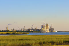 Industry and Nature. A Paper mill on a marsh with blue water and clear blue skies Stock Photos