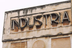 Industry. Old vintage inscription italian sign. An inscription on a sign with the word in Italian Industry. An old abandoned factory in Italy. Concept of royalty free illustration