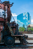 Industry past, present and future. A broken and abandoned coal burning locomotive stands in the shadow of a modern world built on steel and glass Royalty Free Stock Images