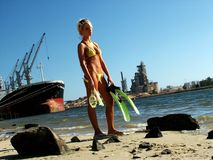 Industrial seaside. A girl with snorkeling gear standing disappointed by an industrial seaside Royalty Free Stock Photos